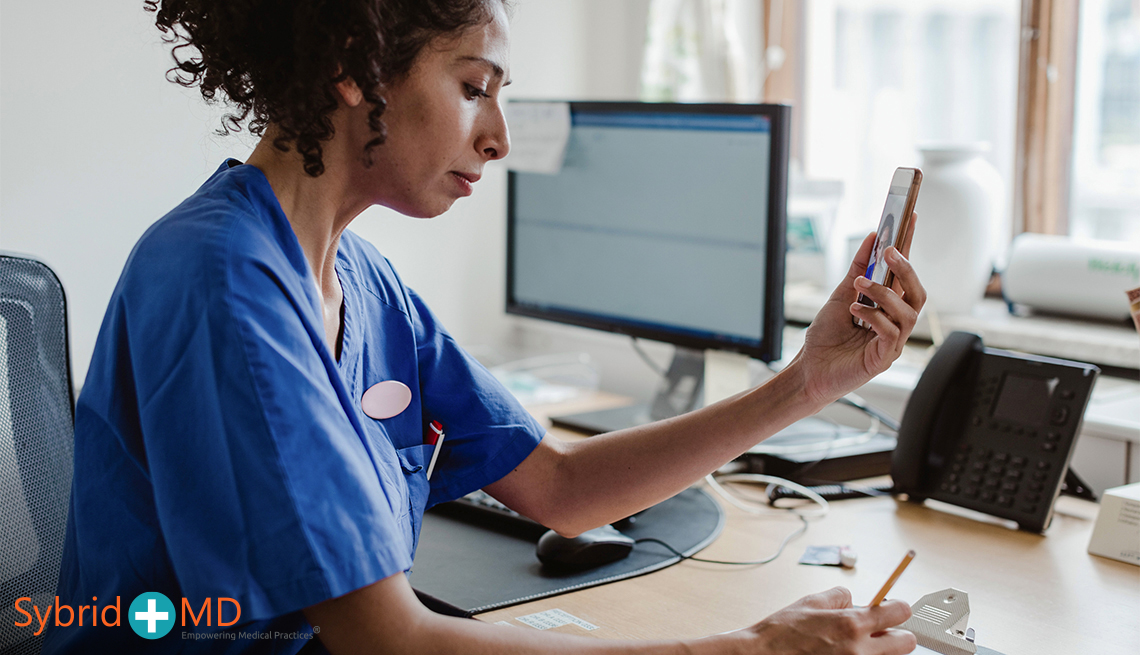 Nurse writing in clipboard while using phone for video conference at clinic
