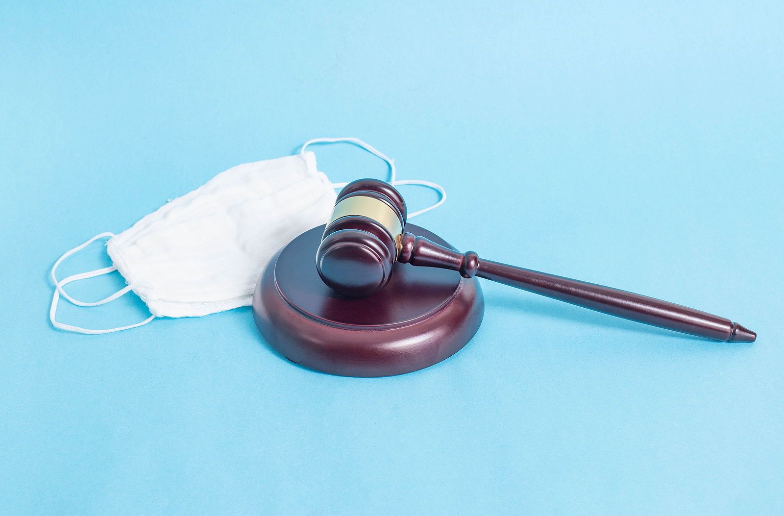 Judicial Gavel And Protective Medical Mask On A Blue Background.